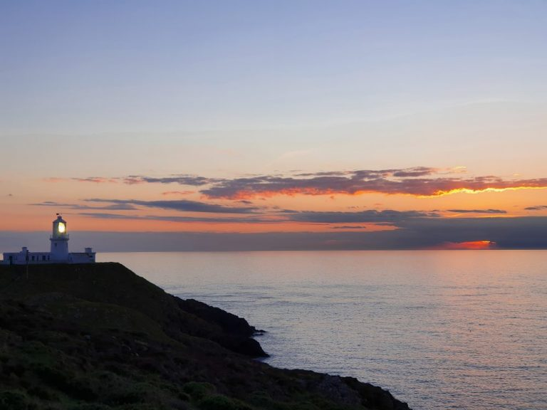 Strumble Head lighthouse lit up with the sun gone down